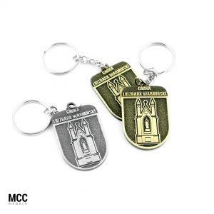 Breloczki z budynkiem w kolorach antycznych wyprodukowane przez MCC Medale