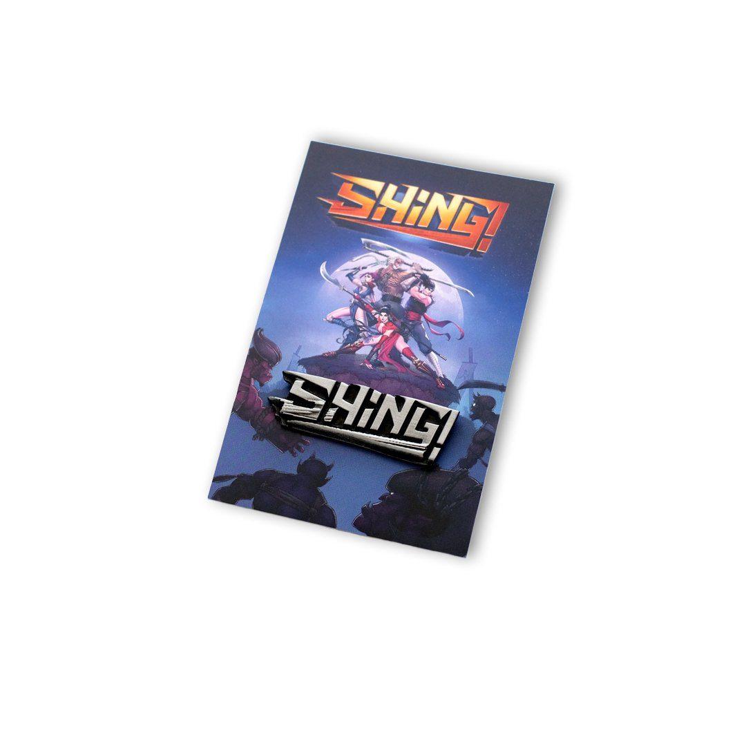 Pins gamingowy umieszczony na efektownej graficznie karcie z gry SHING!, wyprodukowany przez MCC Medale
