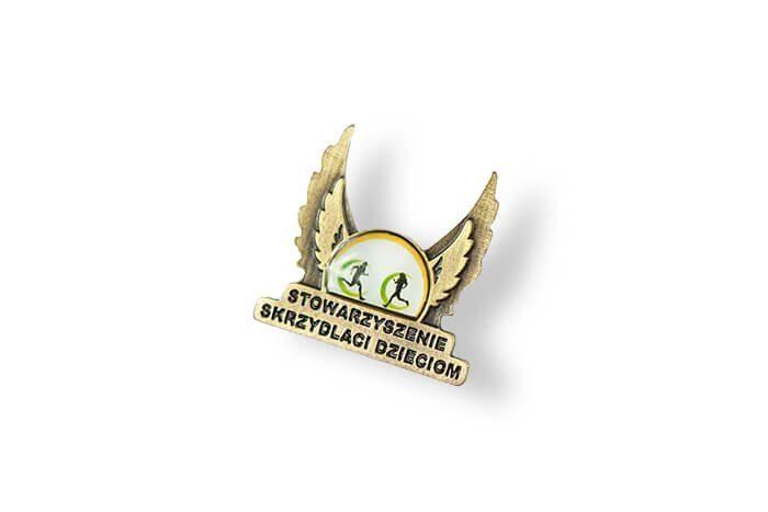 Pins Stowarzyszenia Skrzydlaci Dzieciom wykonany przez producenta pinsów - firmę MCC Medale