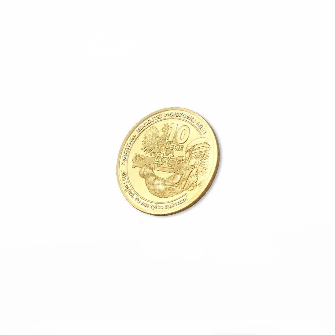 Moneta bita w kolorze złotym z motywem żołnierza oraz godła Polski