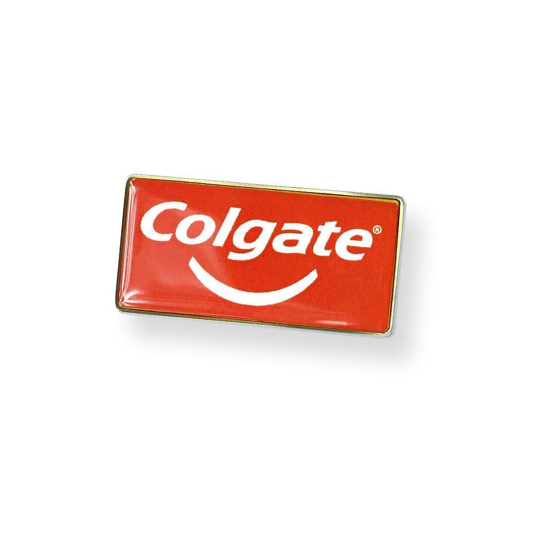 Przypinka firmowa z logiem Colgate na czerwonym tle